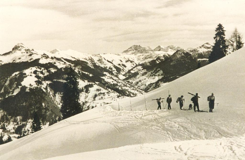 """Gäste und Träger bei der Anreise in unser """"Ur-Skigebiet"""" Bergland ca. im Jahr 1950"""