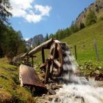 Die Kraft des Wassers wird auf der Alm genutzt zum Butterrühren am Wasserrad