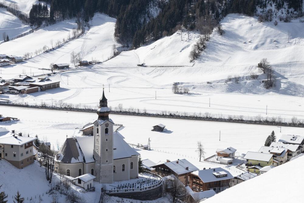 Großarler Kirche mit der Loipe im Hintergrund